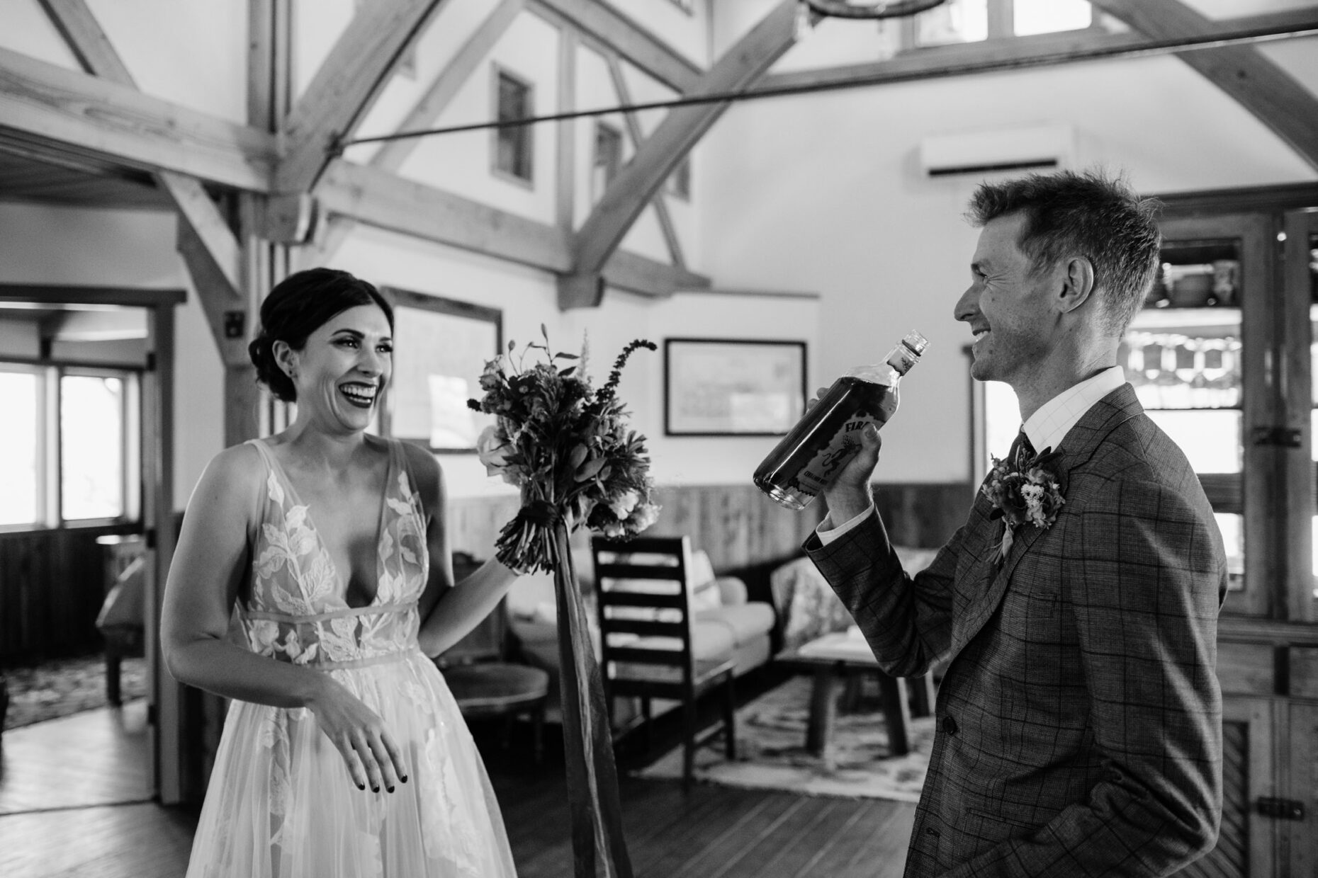 Fun candid photo of bride and groom drinking together on their wedding day