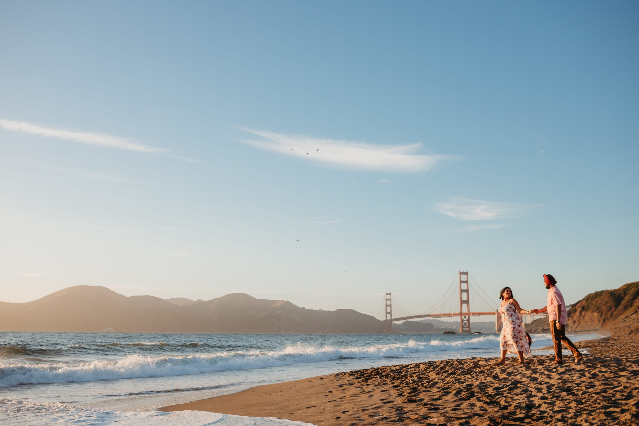 couple walking along the beach at sunset with golden gate bridge in the background