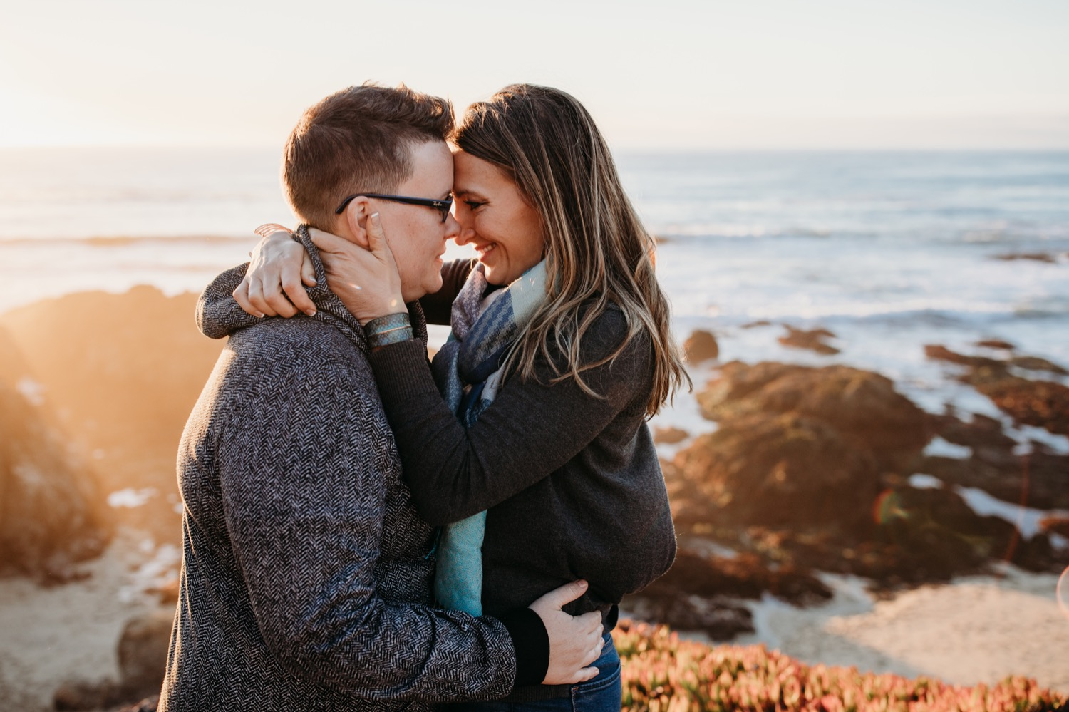 Bodega Bay, California. Bodega Bay Trailhead hike. Sunset beach Engagement Session. Couple hugging with foreheads touching on a rocky mountain. Rocky mountain above an ocean.