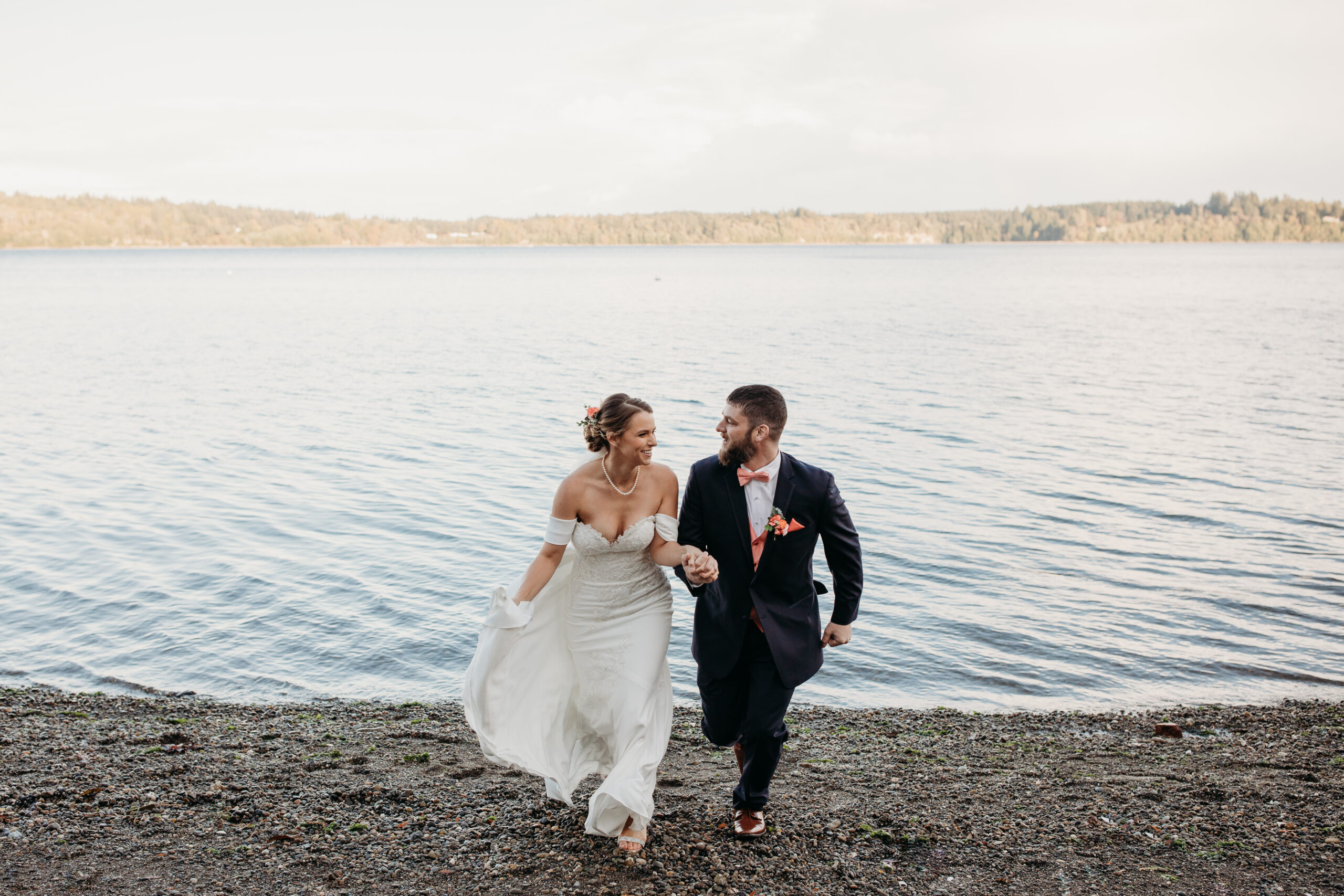 couple holding hands, looking at. each other and running towards the camera at a lakefront private property in Washington State.