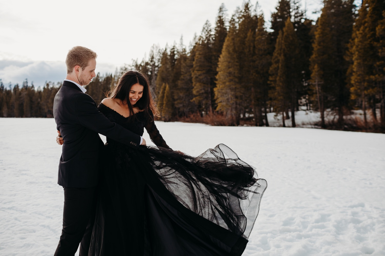 Couples in all black outfits against the snow. dancing lifting in meadow full of snow