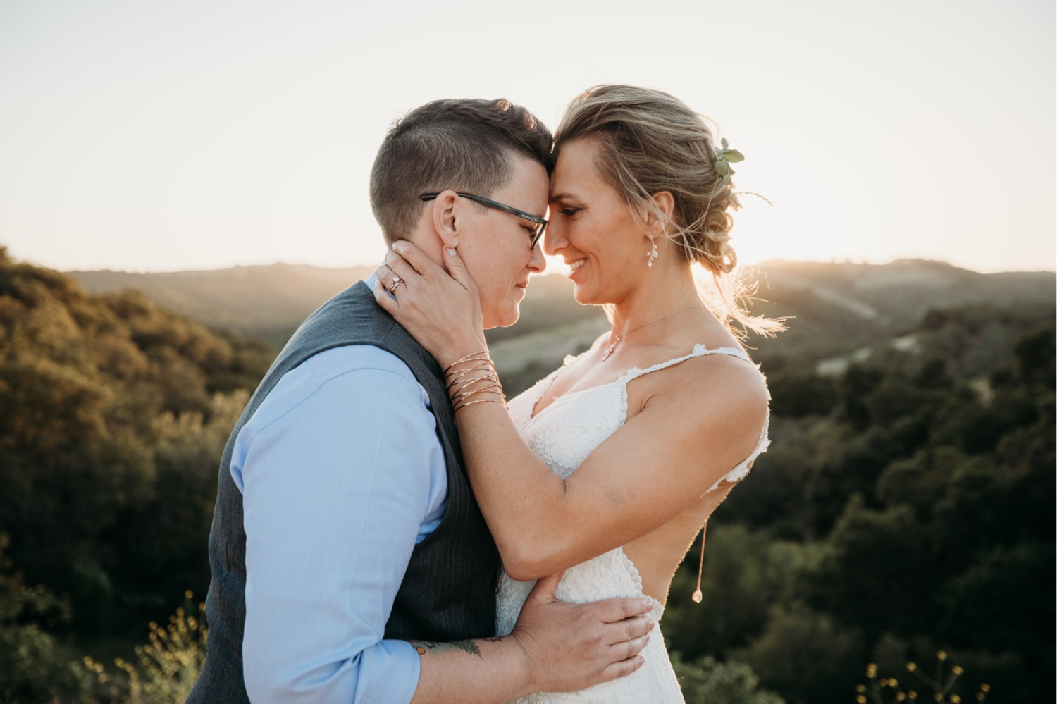 The Trailer Pond at Alta Colina. Paso Robles Wedding Venue. Same Sex Wedding. LGBTQ wedding. Couple hugging with foreheads touching each other on top of a mountain. Terrain.