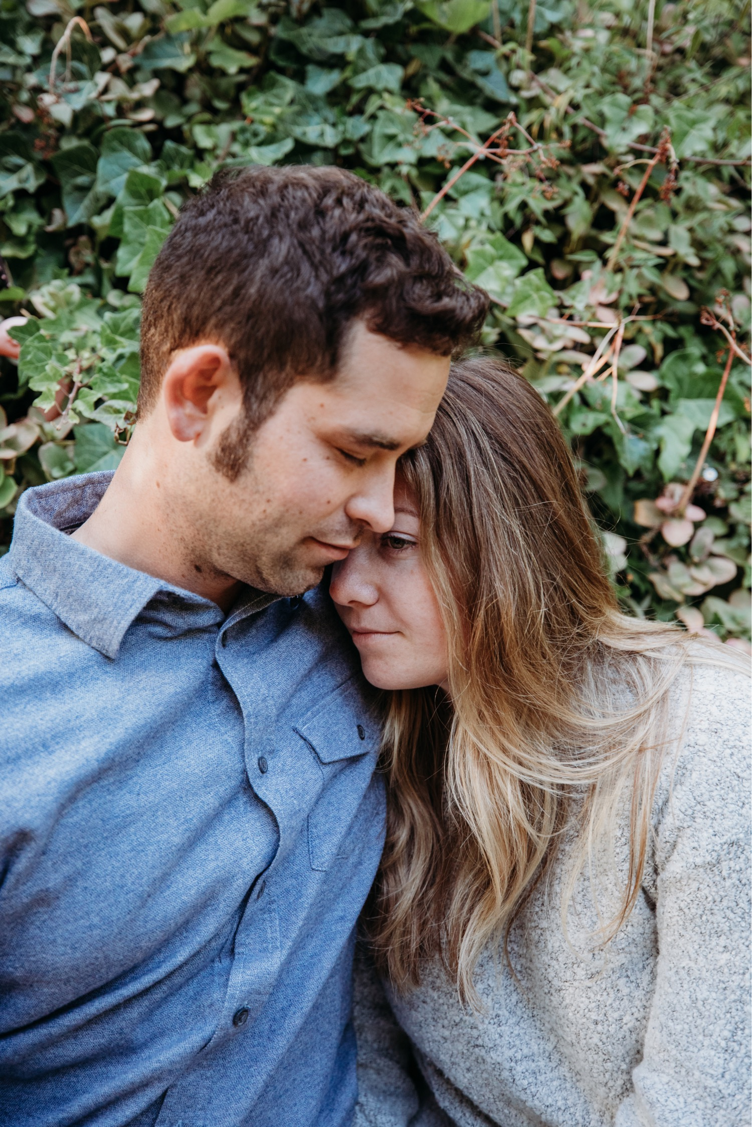 Woman rests her head on her fiance's shoulder in their Big Sur engagement photoshoot