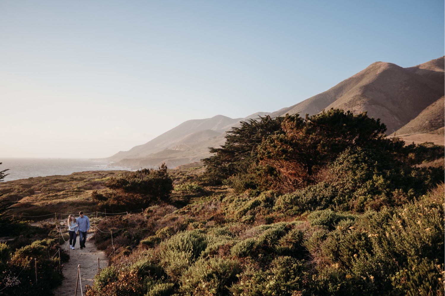 Couple walks along a trail at sunset in Big Sur, California on their engagement photoshoot.