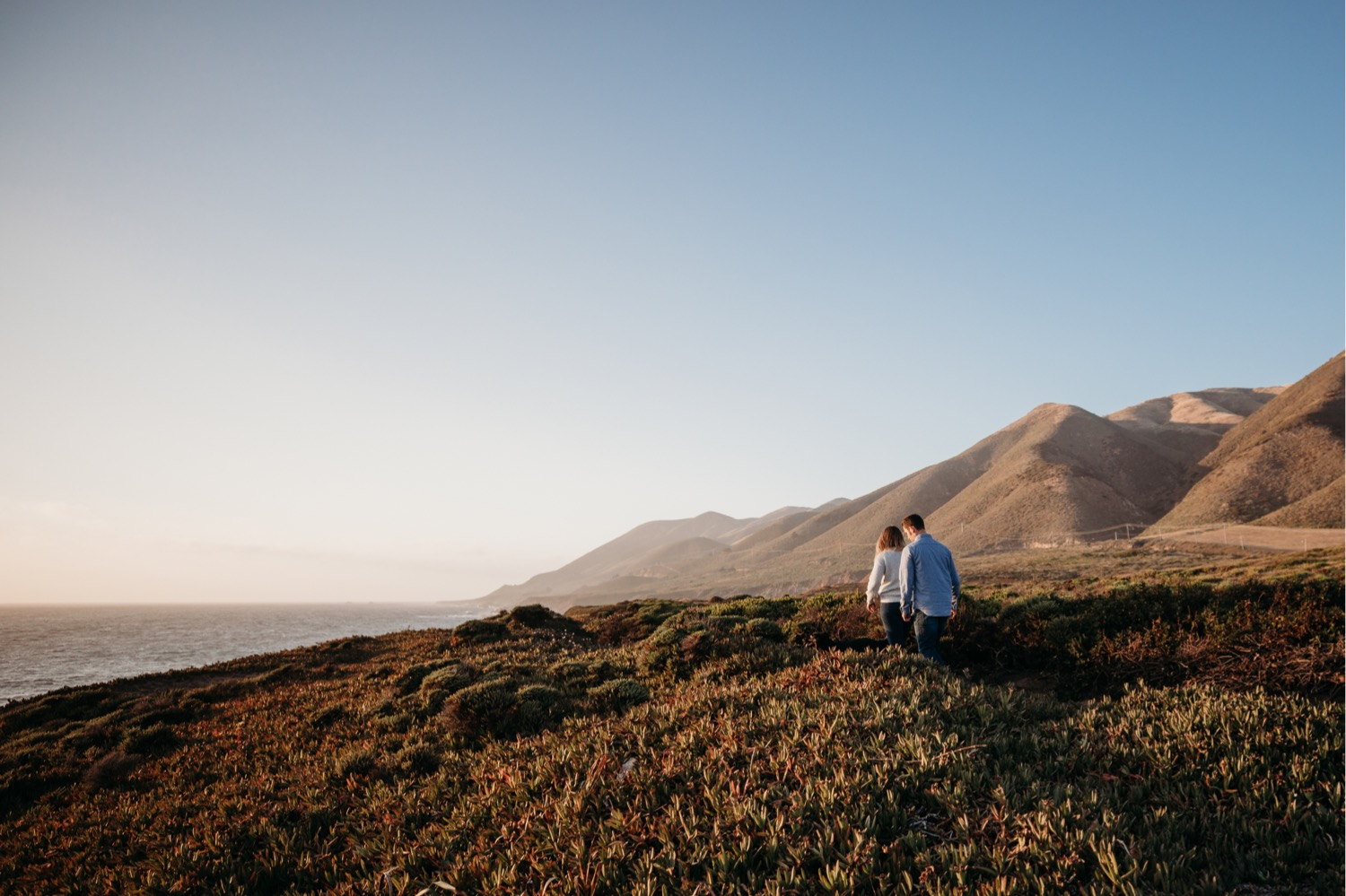 Couple walks along a bluff in Big Sur at sunset on their engagement photoshoot in California.