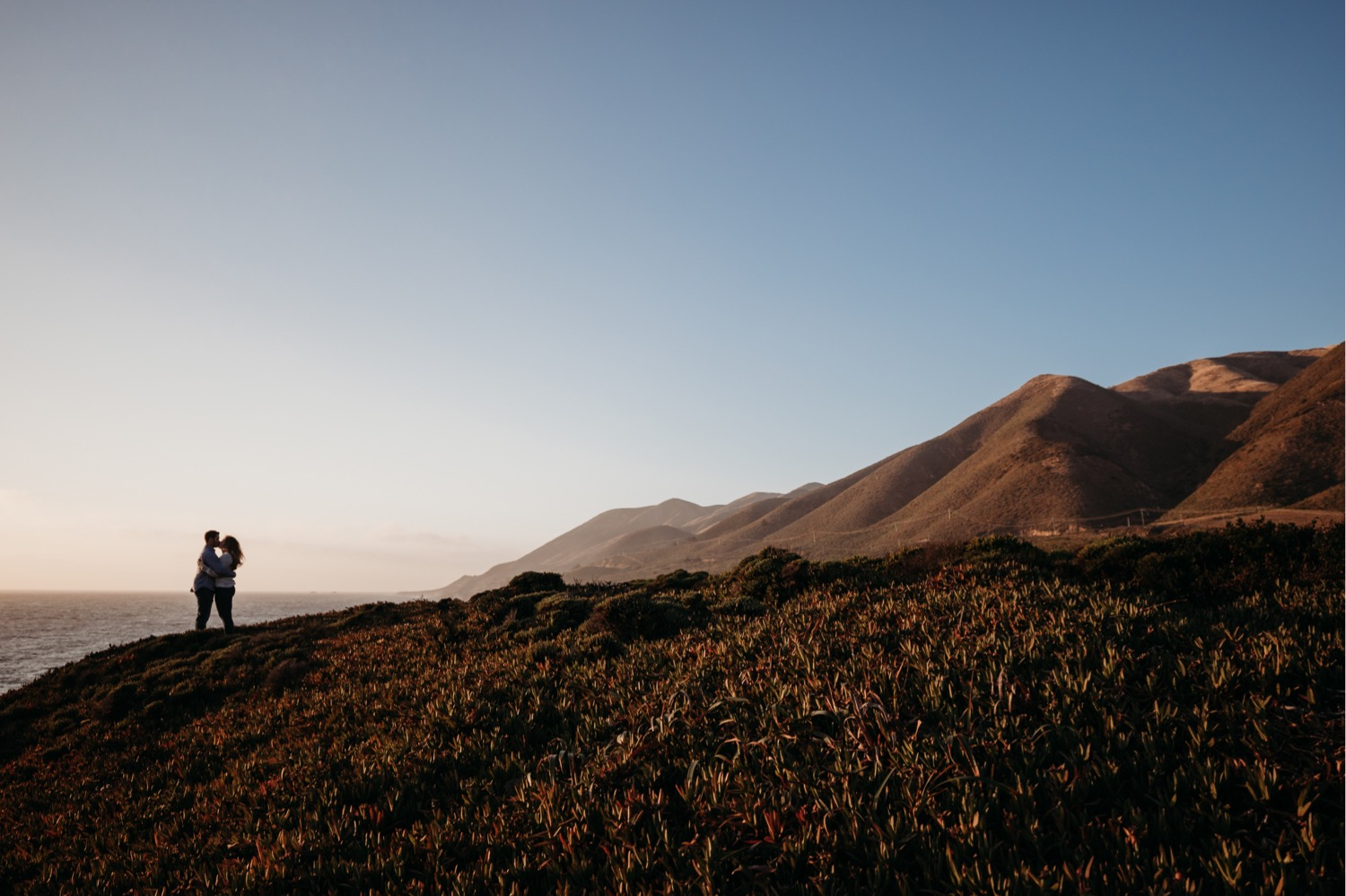 Couple kisses on a bluff at sunset during their Big Sur, California engagement photoshoot.