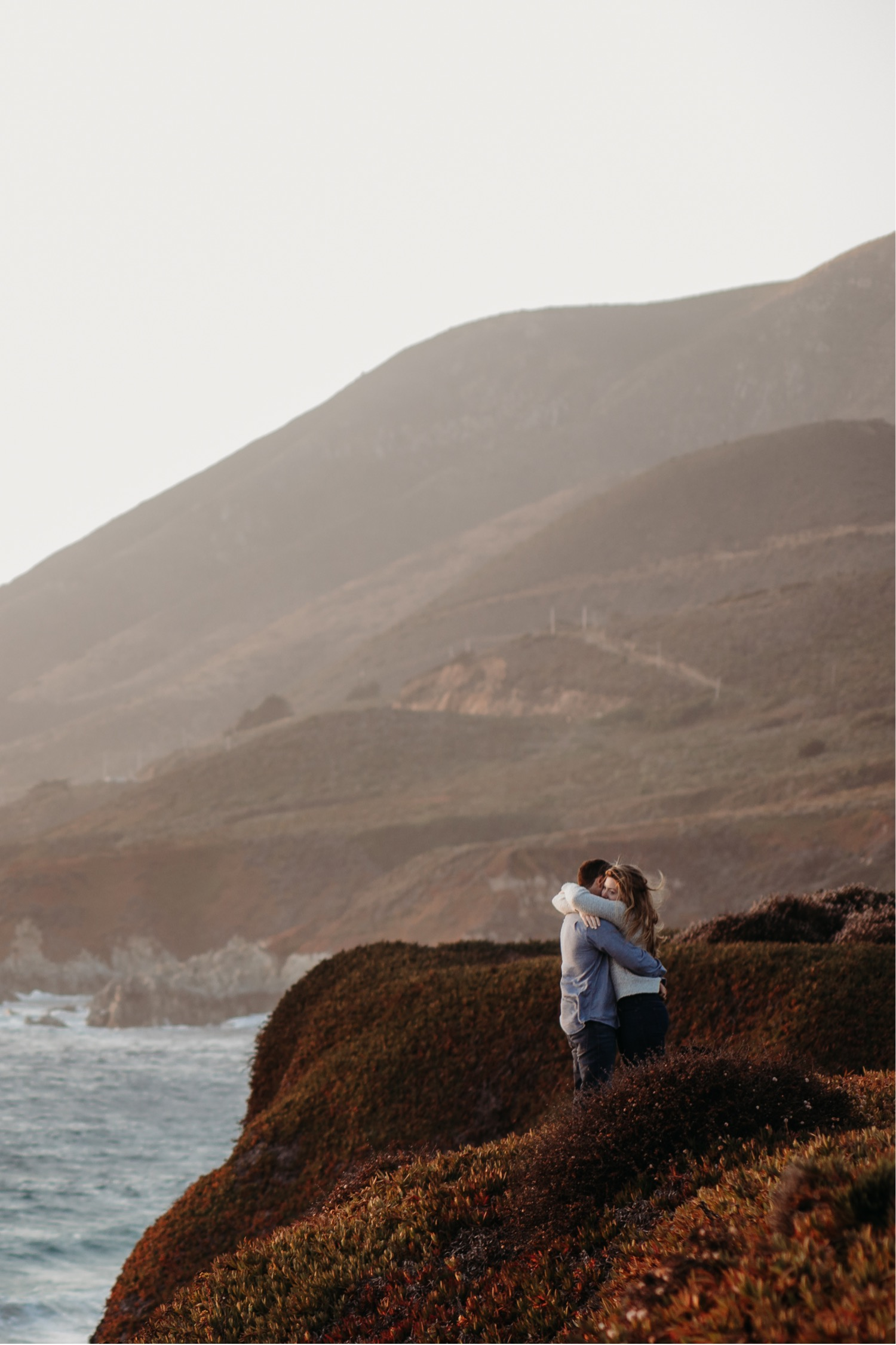 Couple embraces in a big hug on a bluff in Big Sur, California during their engagement photoshoot.