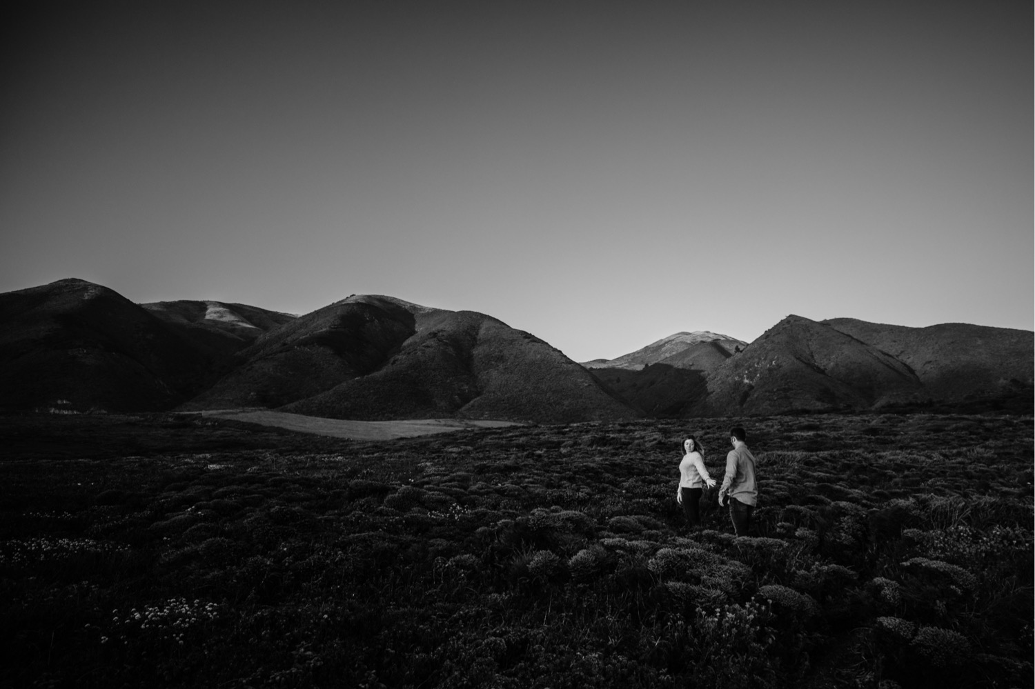 A black and white photo of a woman leading her fiance down a Big Sur hiking trail by hand during their engagement photoshoot in Big Sur, California.
